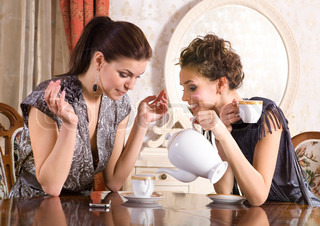 Two girl-friends talk and drink tea in drawing room