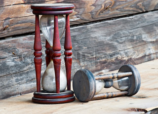 Two old dusty wooden sand clocks, on wooden background