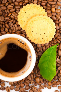 Coffee beans, green leaf of coffee plant with cookies and cup of coffee. Focus on beans