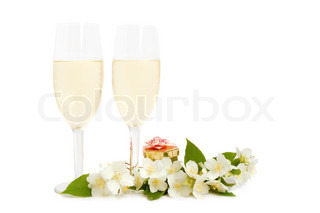 Pair of champagne flutes, fresh jasmine flowers and box with gift on white background