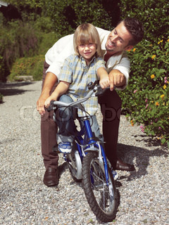 father with kid and bike