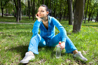 Pretty young girl runner in the forest with bottle of water
