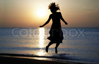 Silhouette of the happy woman jumping and dancing at the sea during sunset. Natural light and shadows