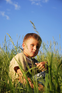 Young boy sitting on green grass under sky