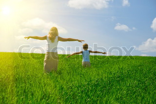 ma and son walk in field. agricultural nature landscape with blue cloud sky and green grass