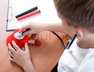 cute young boy playing doctor with stethoscope