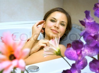 beautiful woman in a bath with petals of flowers