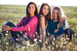 three young beautiful woman sitting in a field on the  sky background