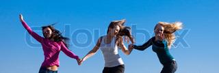 tre unge smukke kvinde hoppe ind i feltet mod himlen
