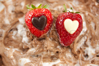 Picture of two strawberries with a heart center laying on mixed up chocolate mousse