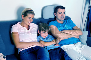 A family watching TV with child on the evening