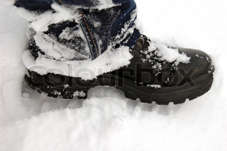 Black boot and footprint in fresh white snow