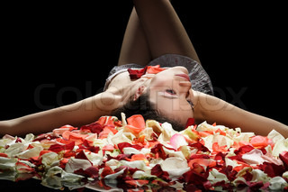 active sexy girl on black background with rose petals