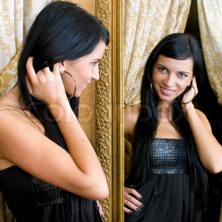 Beautiful young woman is looking at the mirror