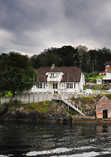 traditional norwegian wooden house standing at the fjords coast
