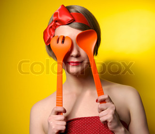 Beautiful pinup style housewife with kitchen utensils
