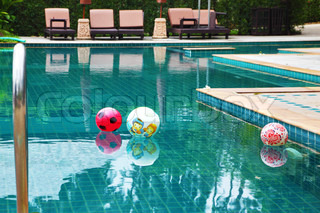 Three beautiful colored balls floating in the clear water of the pool at the hotel. Koh Samui