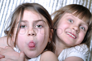 close-up portrait of two playful 6-7 year old girls