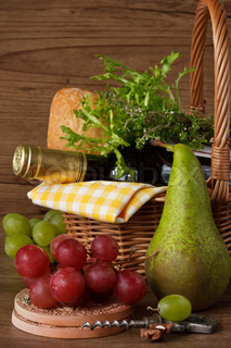 Wine, bread and herbs in a wicker basket, grapes and pear for picnic.