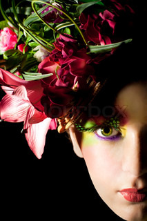Close up portraite of beautiful woman with creative flower cap. Artistic makeup with long feather artificial eyelashes and bright colorful eyeshadow