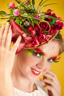 Beautiful young woman with creative flower cap. Artistic makeup with long feather artificial eyelashes and bright colourful eyeshadow