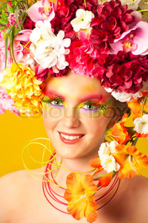 Flower Girl. Beautiful young girl wearing flower wreath. Creative makeup with long feather artificial eyelashes and bright colorful eyeshadow