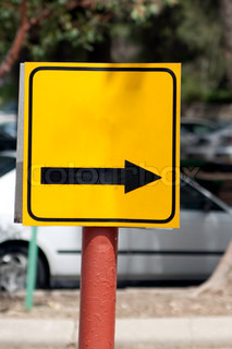 Yellow sign with a black arrow