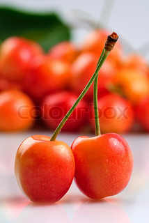 Two sweet cherries crosswise on white with fruit background