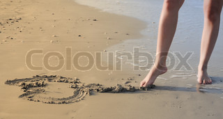 Abstract image of a foot drawing a heart in the beach sand