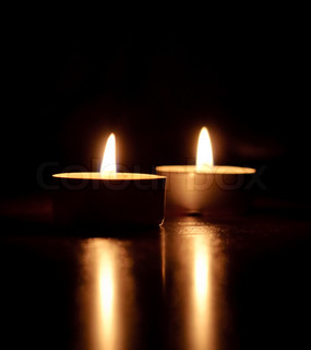 Closeup of burning candles isolated in front of black background