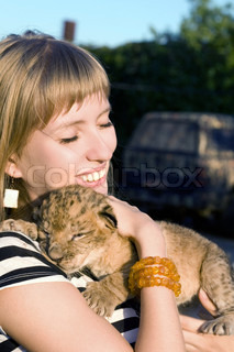 Portrait of young woman playing with lion cub