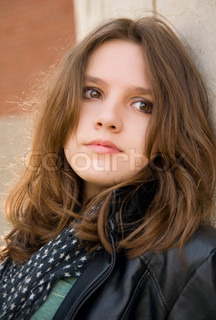 Portrait of the beautiful teenage girl on a brick background