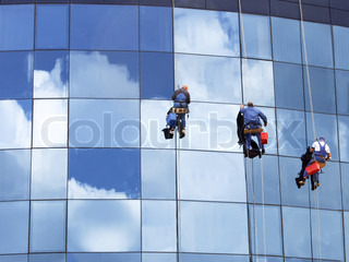 Workers of steeplejack washing a skyscraper windows