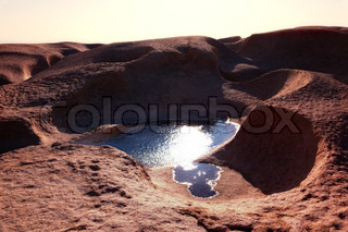 Water in the desert mountains and sun glare