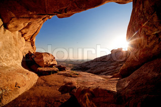 Entrance to cave and the sunset in desert mountains