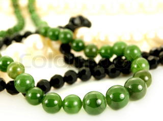 Green emerald stone necklace over black and white pearl necklaces isolated towards white