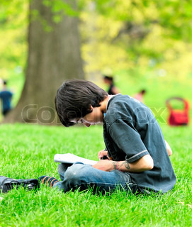 The boy the teenager holds a writing-book in a lap and draws sitting on a green grass in park.
