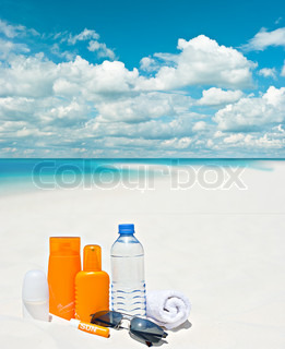 sun protection cream on beach background. blue cloudy sky