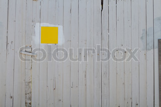 White painted wooden fence with blank yellow sign on it.
