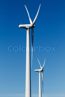 Two great white wind turbines on a deep blue cloud free background