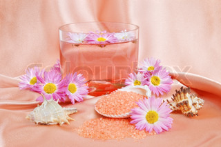 A bright pink spa and body care background. Salt and flower floating in glass bowl.