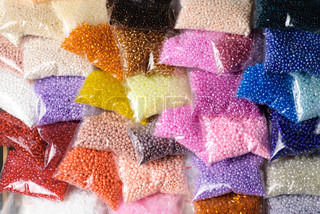 Colorfull glass beads' batches in plastic bags for beadwork in craft shop