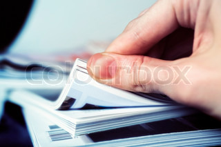 Man's hand turned over a stack of magazines closeup