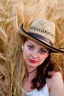 Girl in wheat field in white dress and stetson hat. Selective focus.
