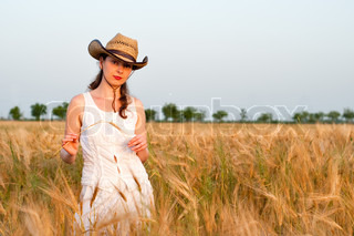 Girl in wheat field in white dress and stetson hat