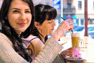 Two girls drinking cappuccino in cafe outdoors