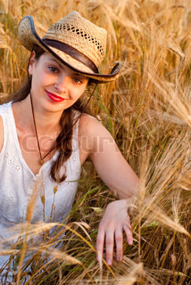 Girl in wheat field in white dress and stetson hat. Soft focus.