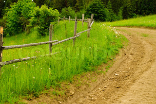 Rural landscape with road and wooden fence