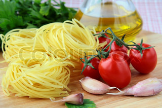 Italian pasta, olive oil and tomatoes on a wooden board