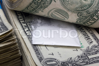 Small sealed bag with drugs laying in a stack of cash.